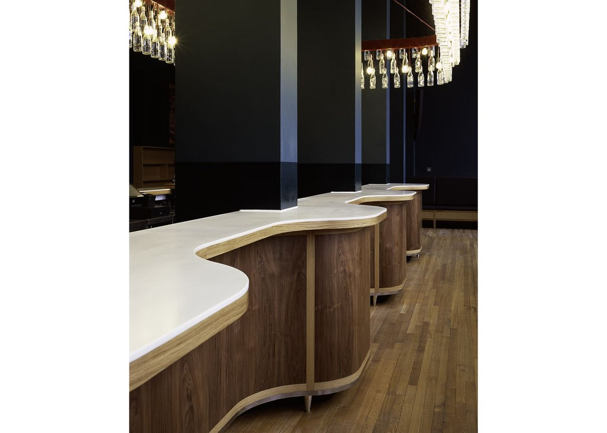 The bar's corian and timber curve around the columns.