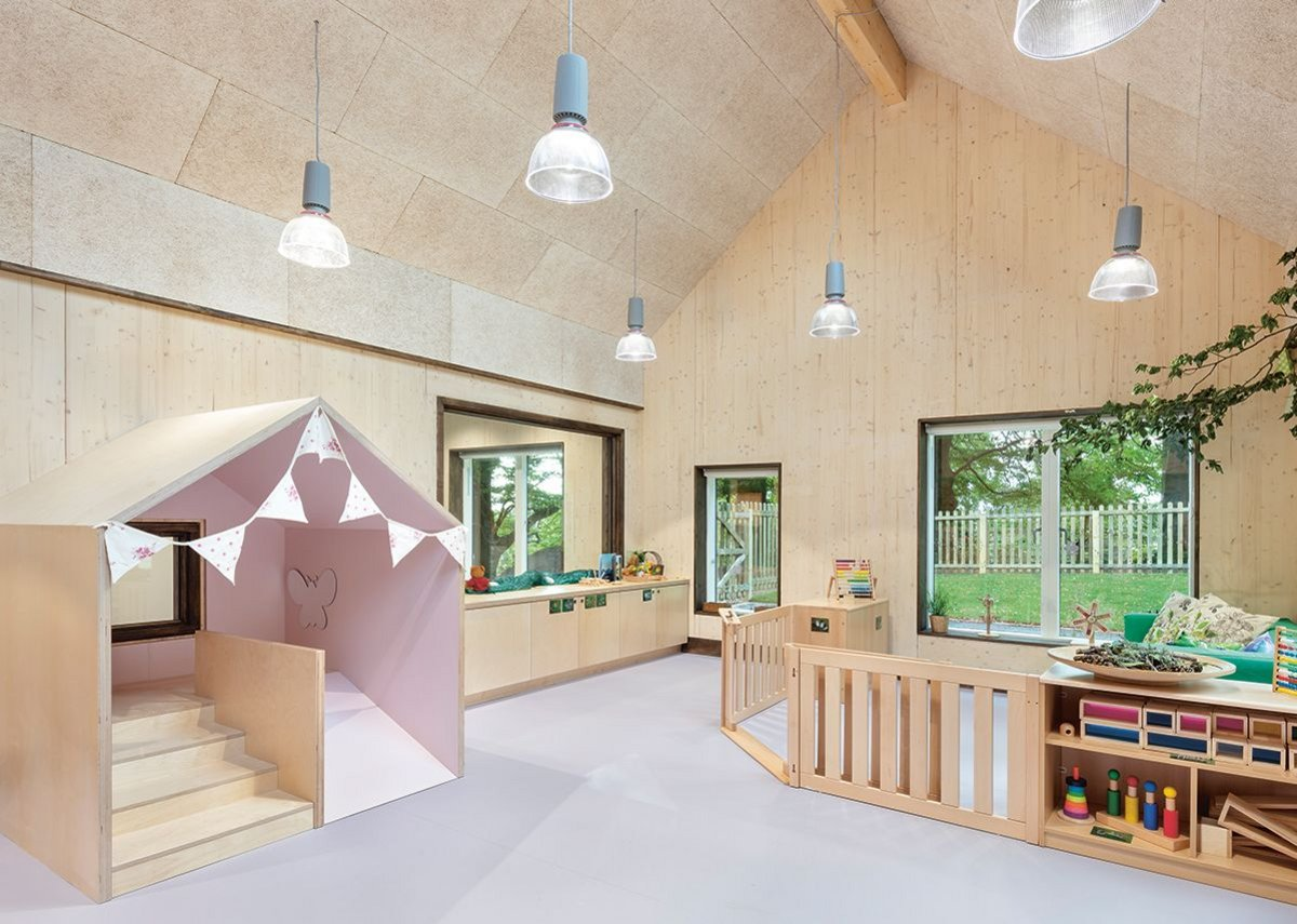 In the baby room, a small house with a short slide mimics the pitches of the classroom volume, which has exposed CLT panels and, on the ceilings, wood, fibre boards.