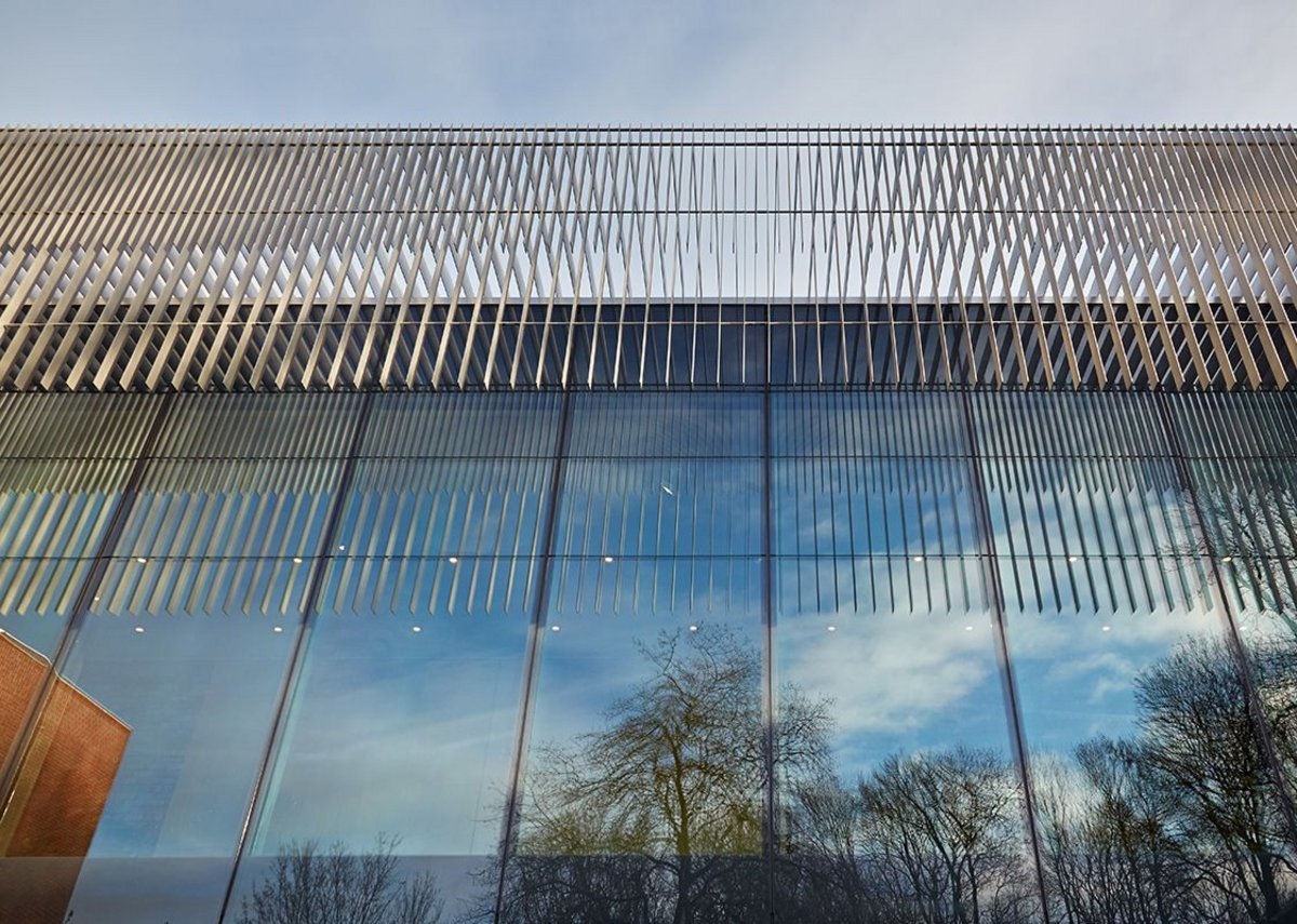 The lighweight brises soleil reflected alongside the park trees.