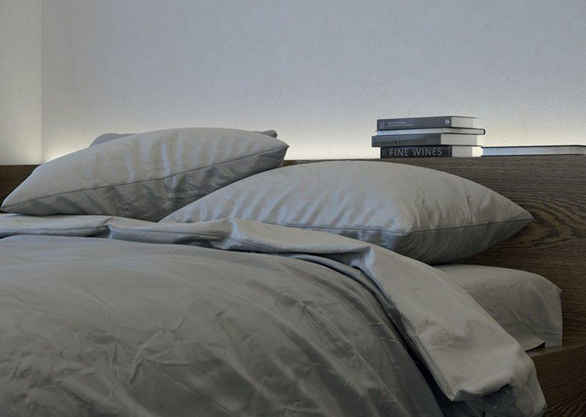 Häfele Loox LED strip light illuminating a bedroom headboard shelving unit.