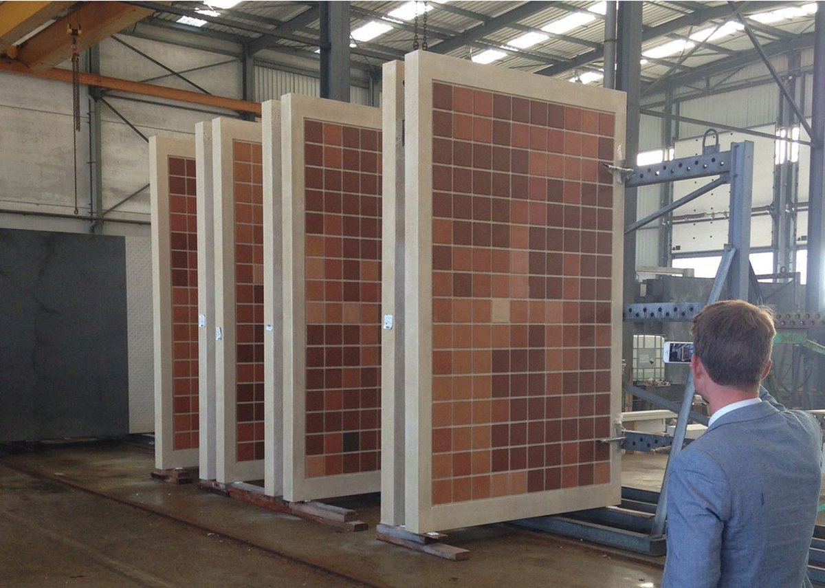 Concrete panels with elements of the L-system design overlaid in terracotta tiles.