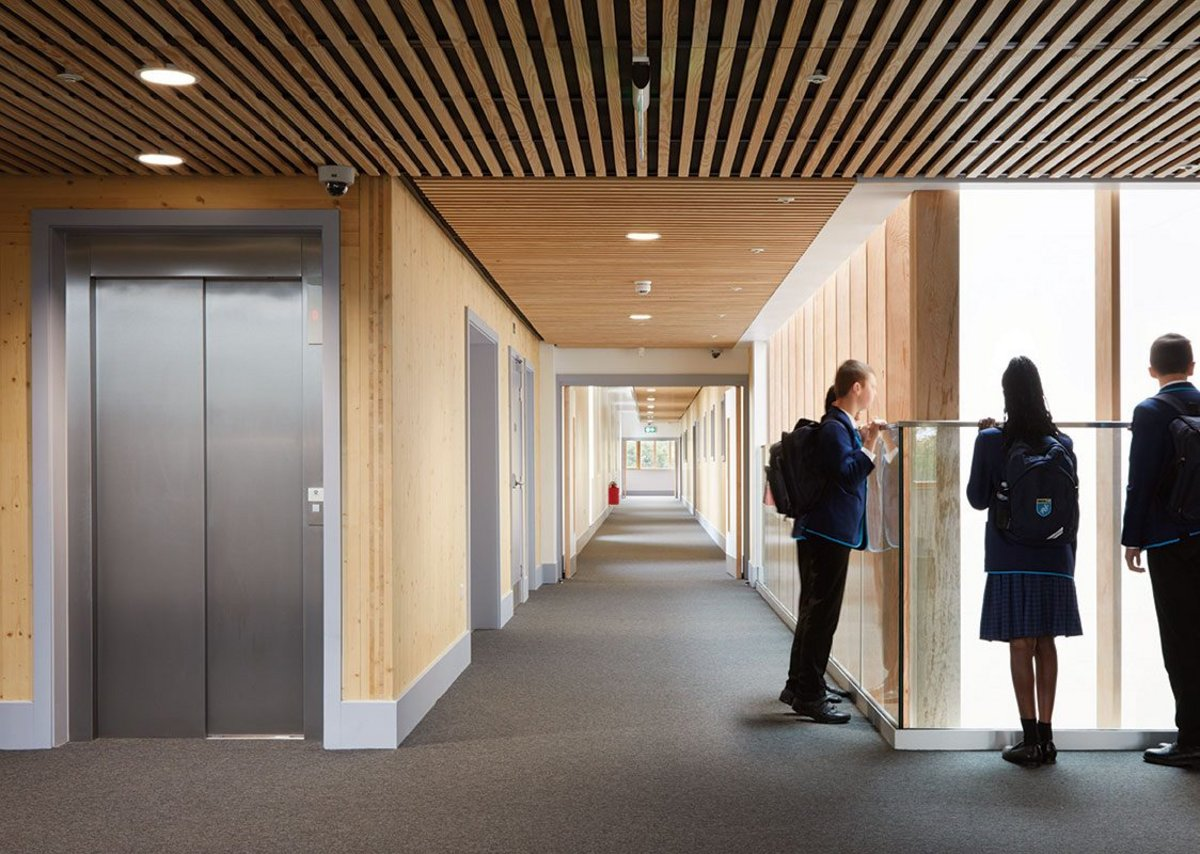 Students can look down into the triple-height library from the timber-lined corridors.