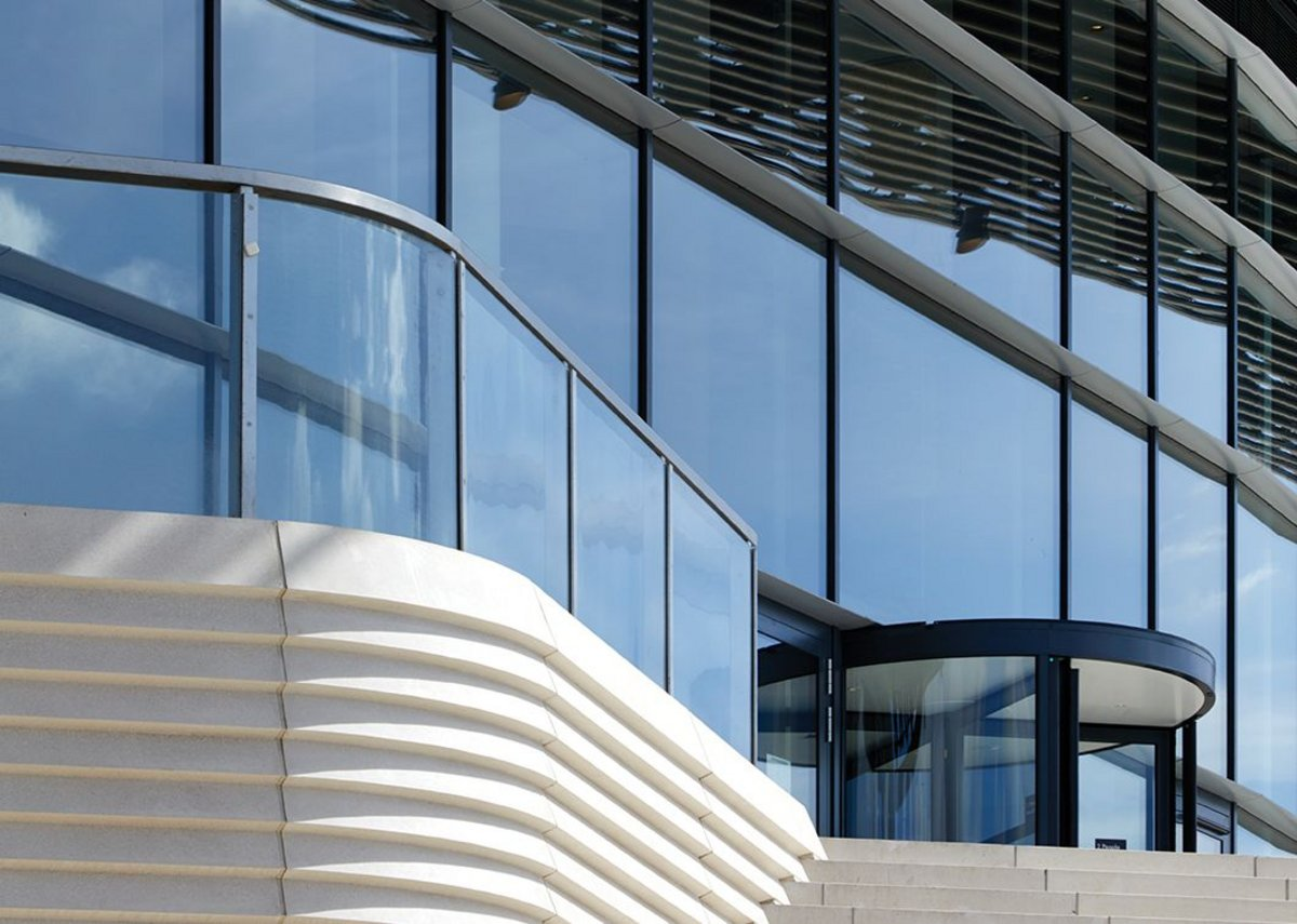The reconstituted stone stair flows into the vertical cladding at ground level.