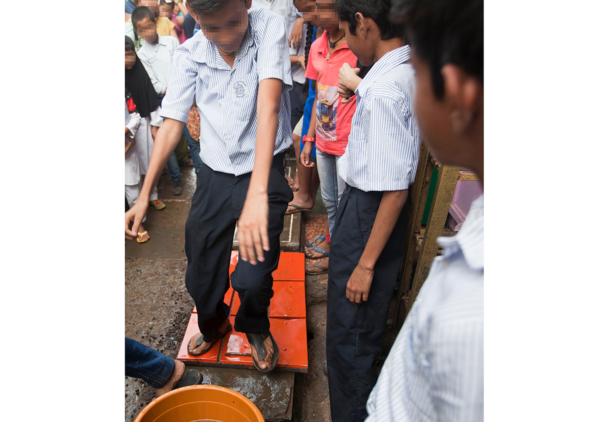 The class demonstrate use of their new gutter cover prototype in the Mariamma Nagar neighbourhood, 2016.