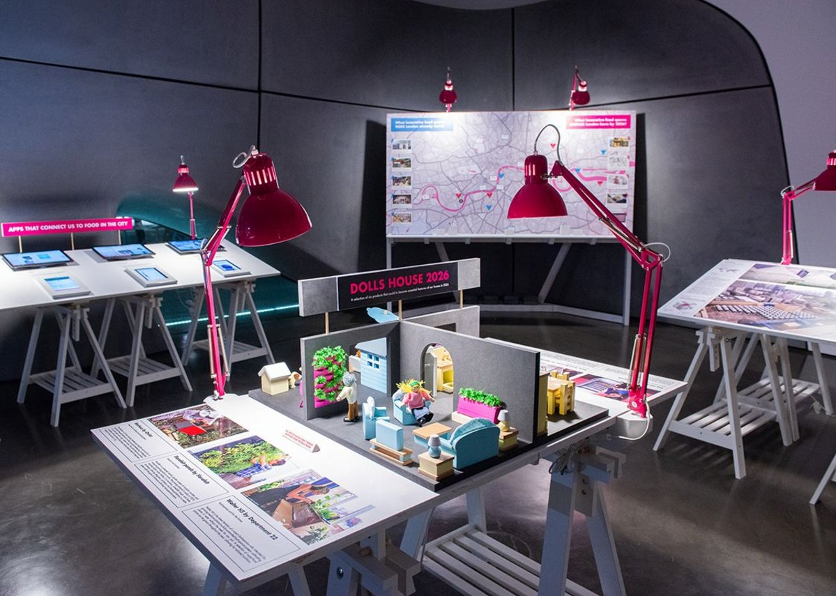 Exhibition installation view of London 2026:Recipes for Building a Food Capital at Roca London Gallery. The image shows a doll's house for 2026 featuring sustainable food products such as in-house hydroponic planting and a food waste recycling unit.