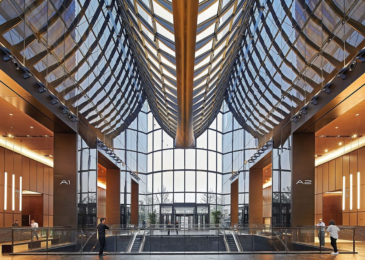 The scalloped exterior form of the cladding becomes a dramatic roof for the office atrium.