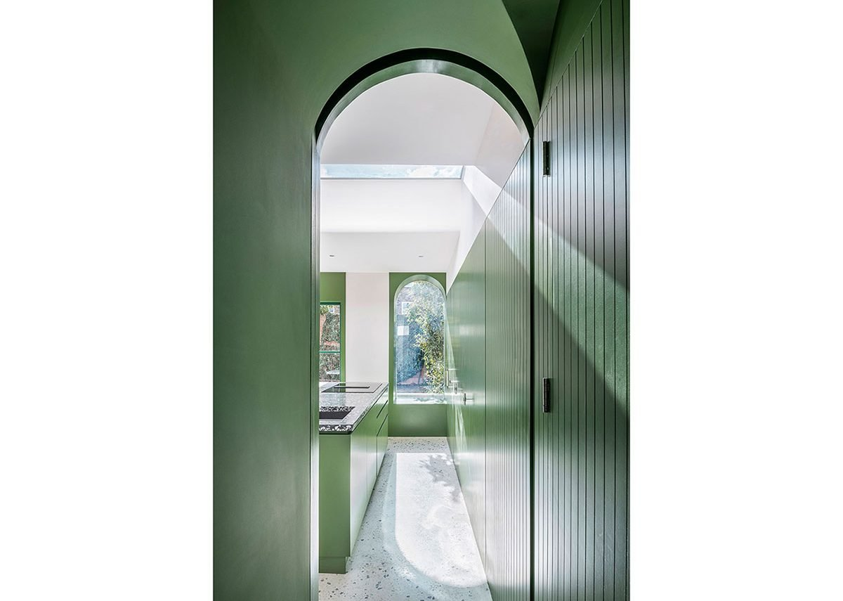 Copious amounts of storage are hidden behind green-painted, timber doors; their grooves suggest the fluting of pilasters.