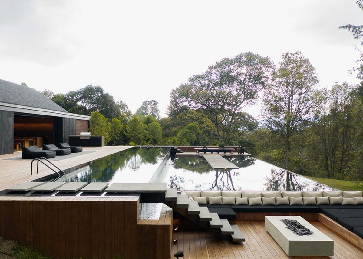 The decking, pool and water mirror with lower level seating area and Neolith Beton fireplace.
