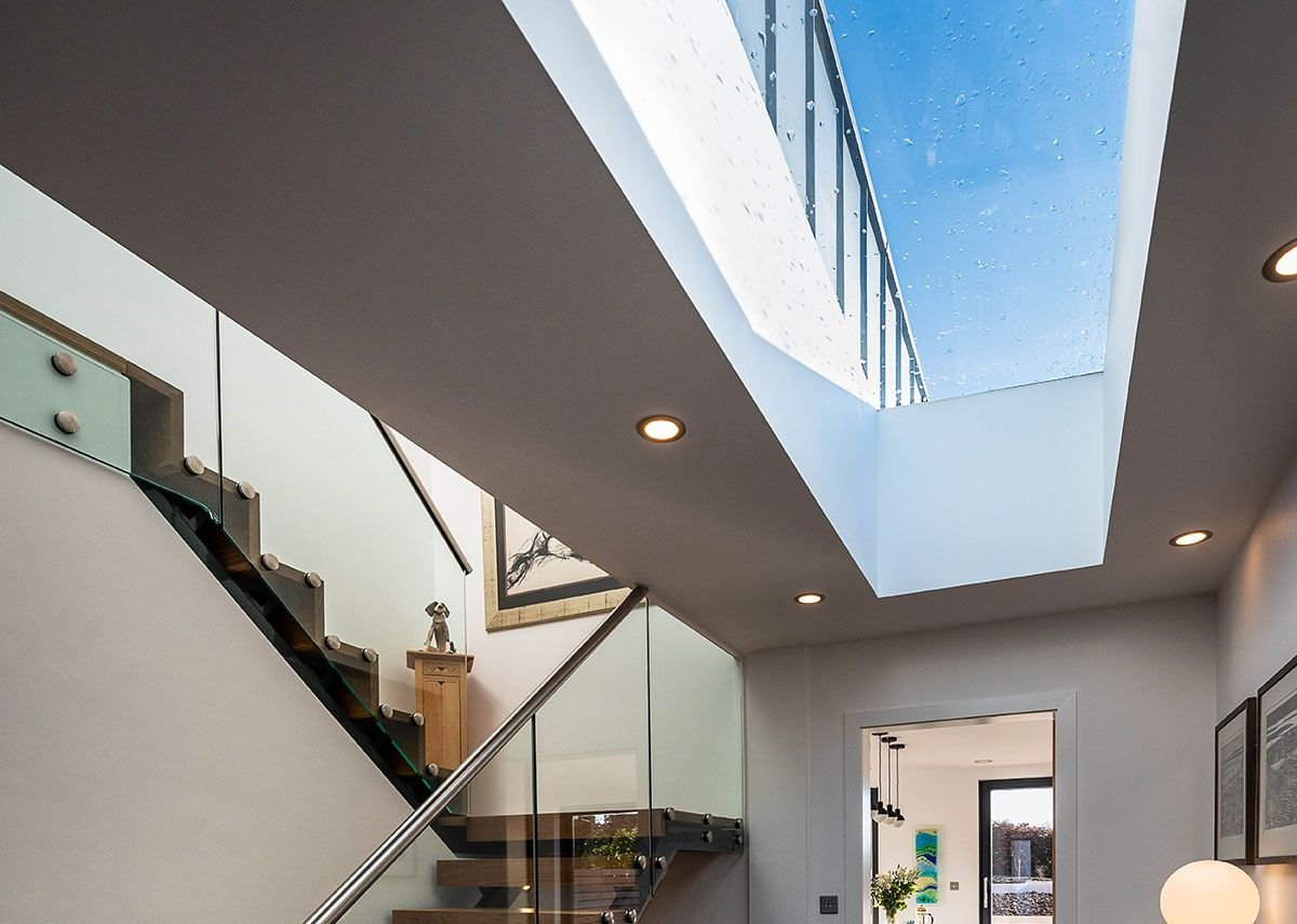 A flat glass fixed rooflight in the hallway opens up to the blue zinc cladding on the first floor, which harmonises with the roofs of neighbouring properties.