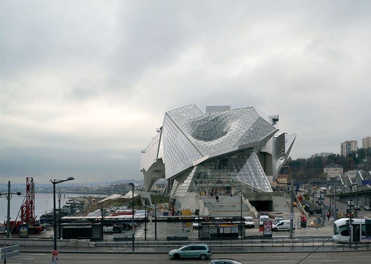 Musée des Confluences, looking south showing the Rhône on the left and the Saône hidden by the rail line and raised autoroute. Sucking down the crystal's roof is the glazed lobby 'gravity well', all accessed from the entrance staircase