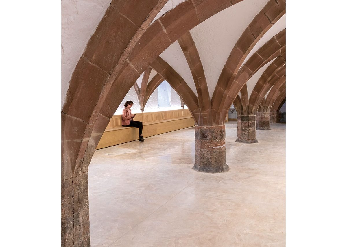 The arches of the undercroft set off by a concrete floor with walls lined by benches.