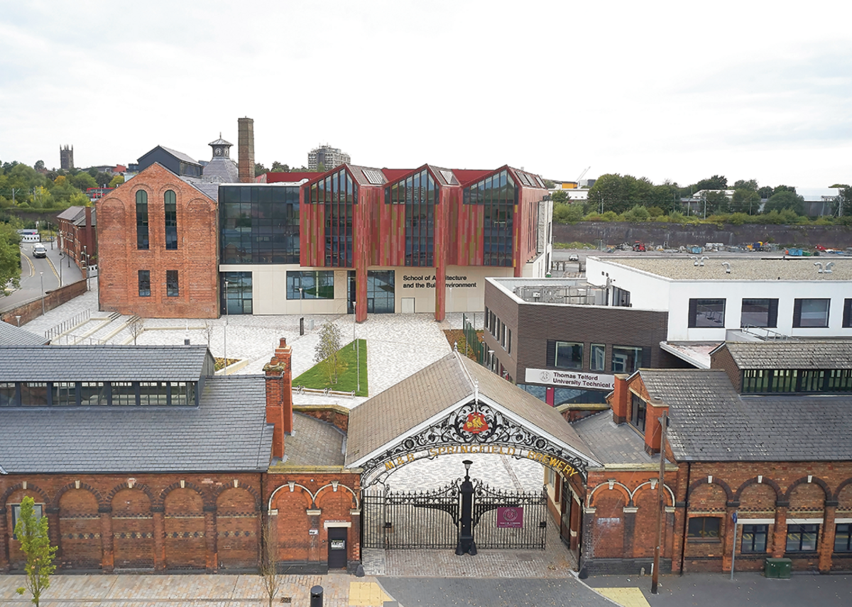 View west past the brewery gateway and stable blocks to the courtyard and new school. The train viaduct is behind with the tower of St Peter's church in the distance.