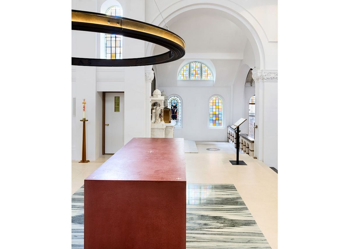A red, Venetian plaster altar, by acclaimed ceramicist Julian Stair is the focal point of the church, below Barr's cast iron ring of light. They sit on top of re-used green marble from the previous high altar.