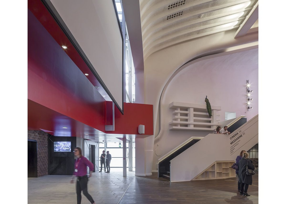 Inside the performance foyer the curves of the art deco cinema take centre stage in contrast with the bold, rectilinear red of the stairs and mezzanine. Chester Storyhouse, Bennetts Associates.