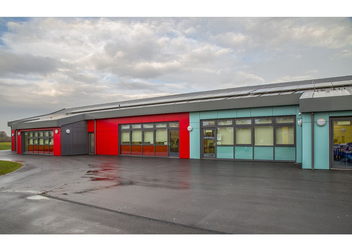 Red and blue Formica rainscreen panels at Barrow Hall Primary School near Warrington, designed by Ellis Williams Architects.