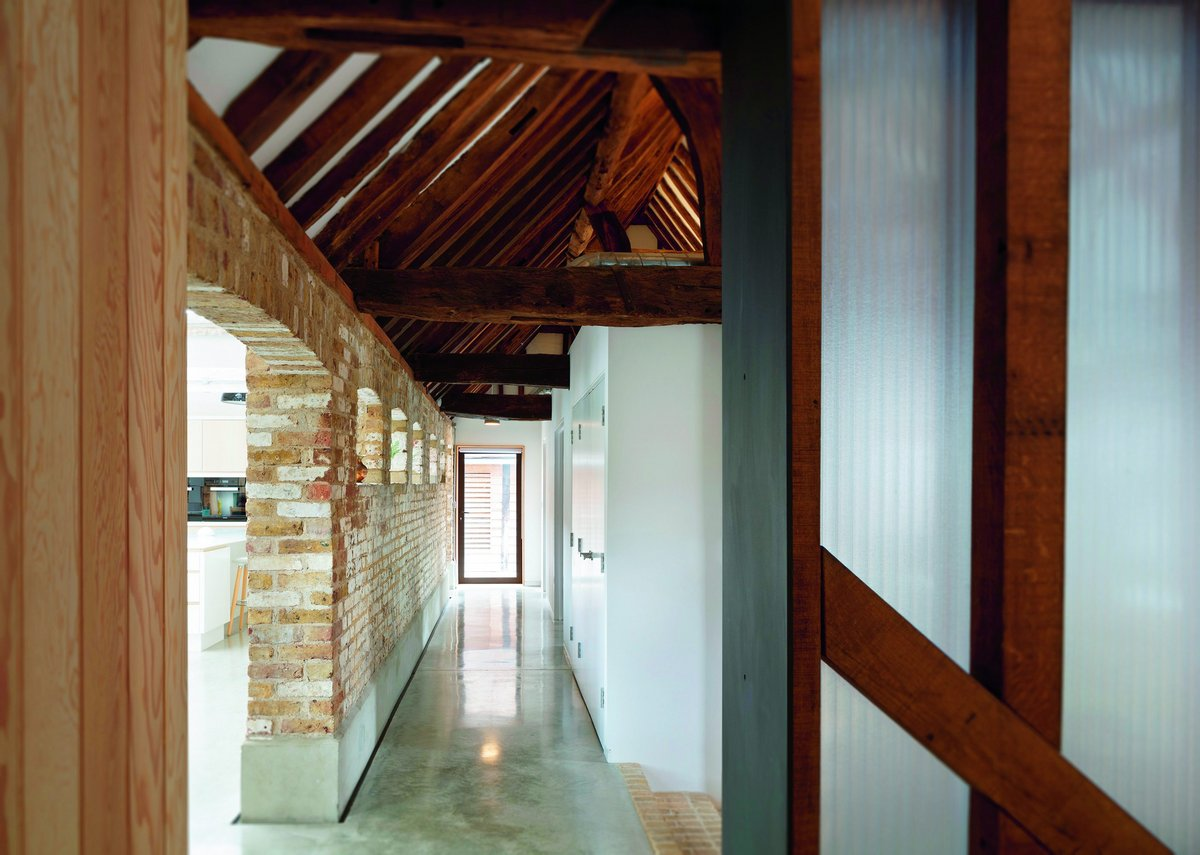 The stepped entrance area leads up to the dairy block's concrete floor  and brick wall – and the kitchen space beyond.