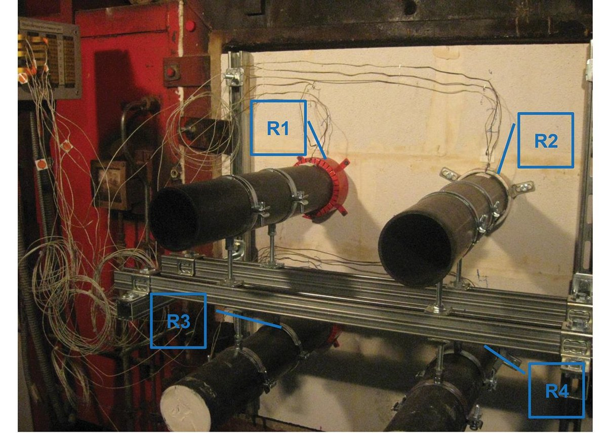The specimen set up, before igniting the furnace, clearly showing pipes, firestop collars and thermocouples.
