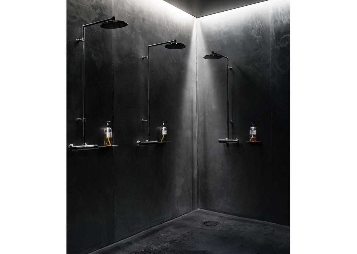 Black downlit concrete showers.