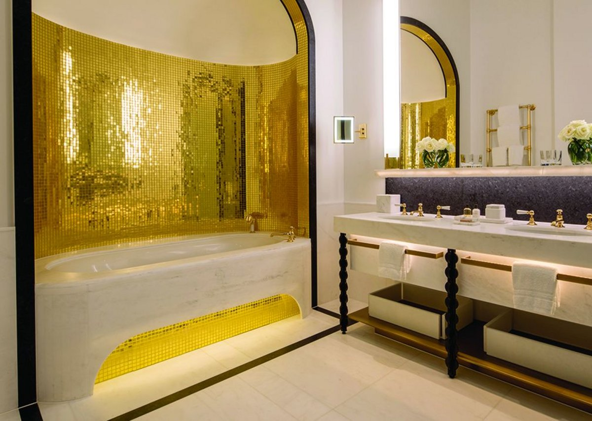 Gold mosaic on curved walls brings an indulgent bling factor to these luxurious spaces.