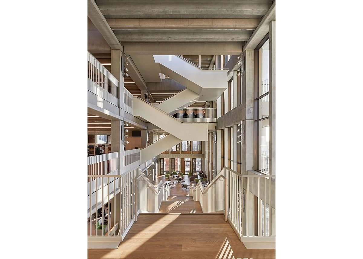 At third floor the concrete staircases along the façade switches to a condensed, steel dogleg staircase. Stage lights bring columns to light on darker days.