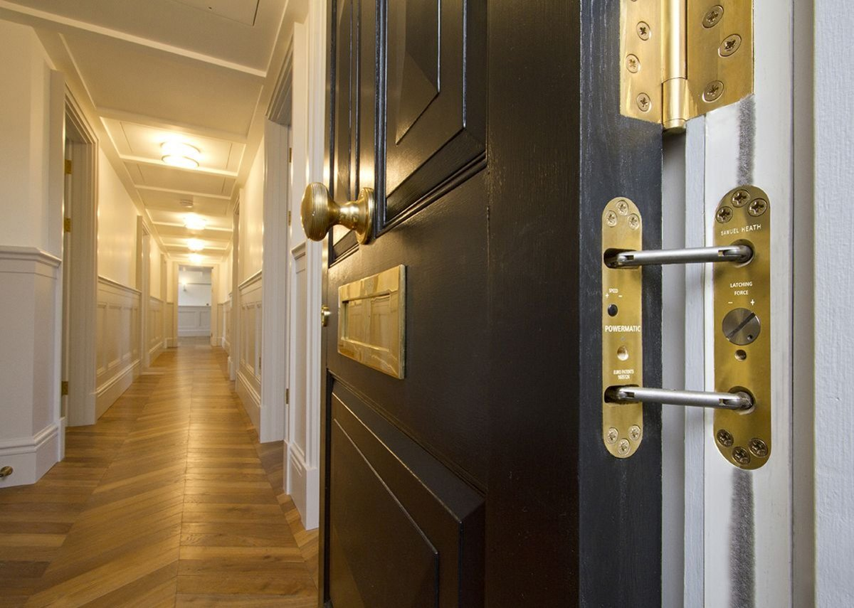 Samuel Heath polished brass door furniture and Powermatic concealed door closer at Leinster Square.