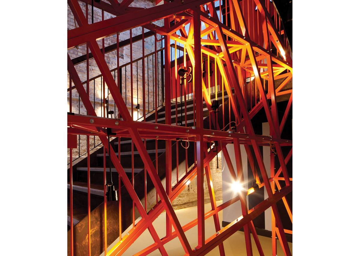 ... and a constructivist flavour to the orange-painted steel latticework staircase in the new atrium.