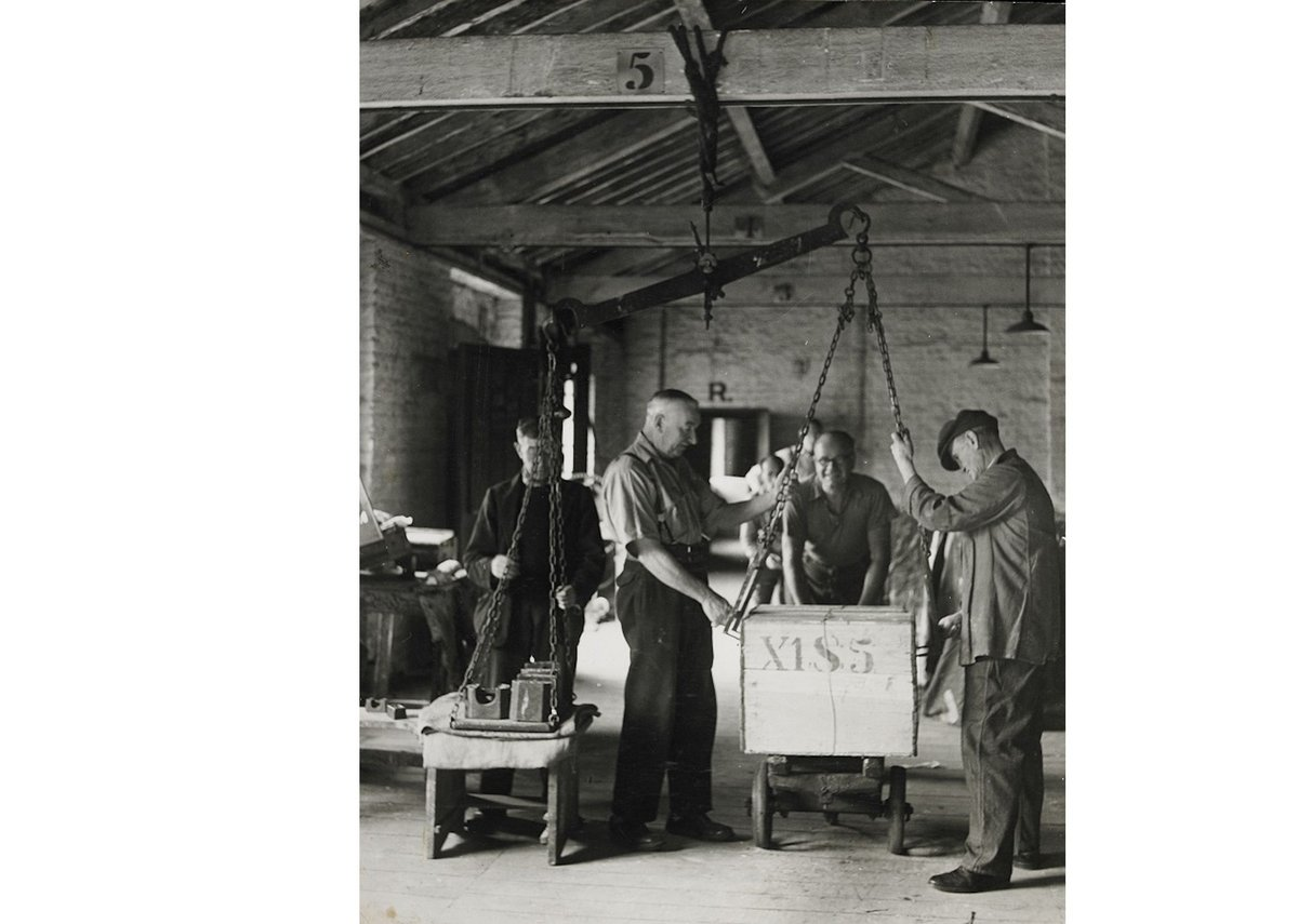 Tea chests being weighed using a beamscale, 1949.