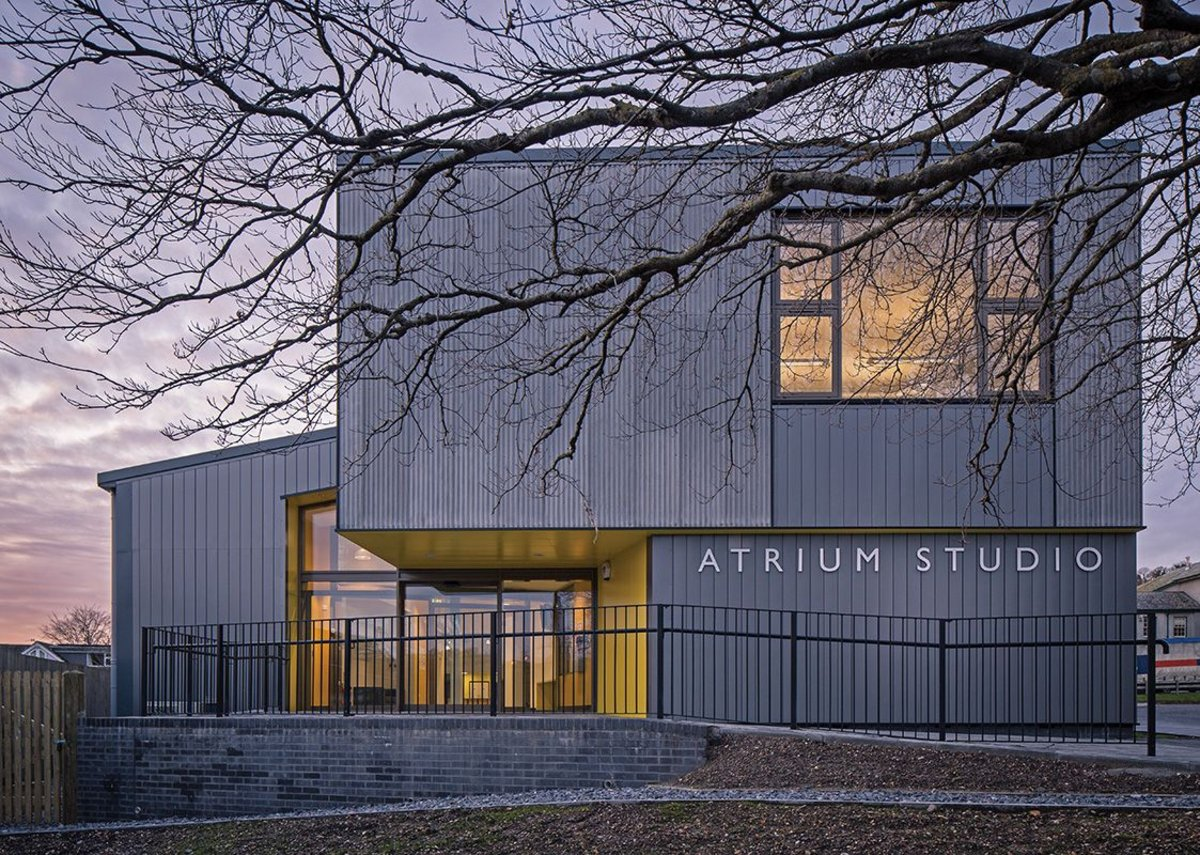 An entrance for students and industry, in glowing yellow below the fibre cement.