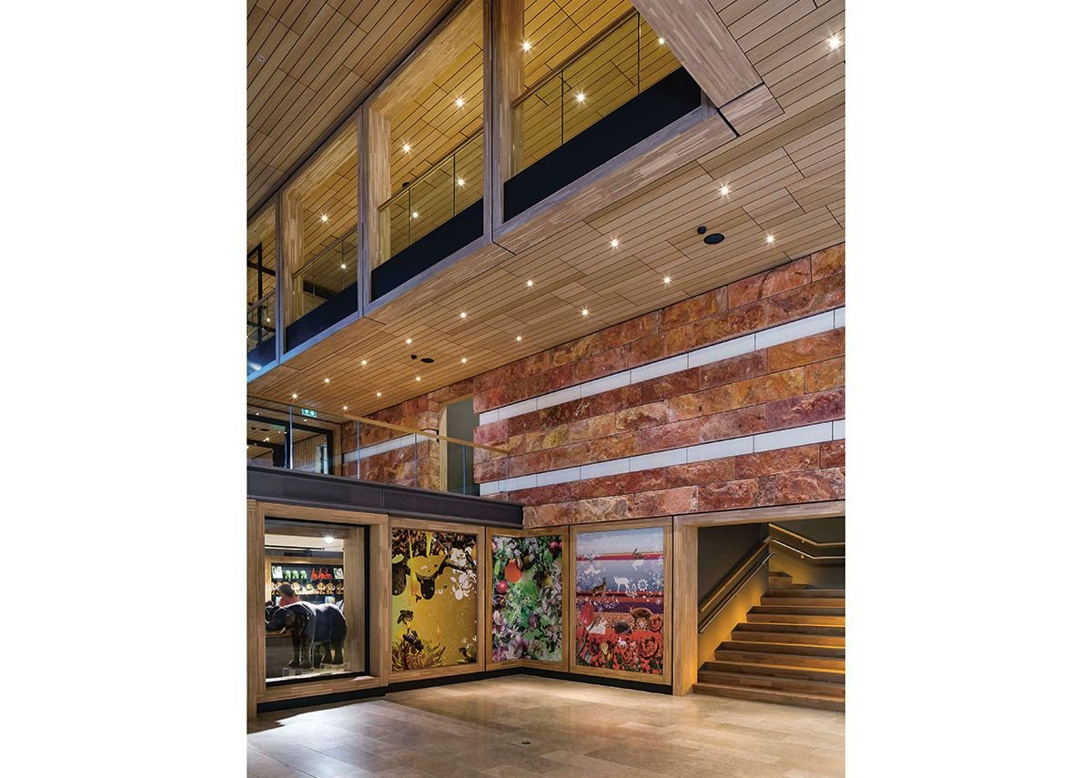 Red travertine, concrete art frieze, limestone floors, timber soffits and treads, Tord Boontje murals; everything is thrown at the visitor at ground floor level.
