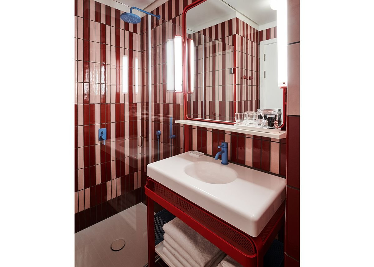 The 70s are referenced on the two-tone striated walls and bevelled edges of the bathrooms.