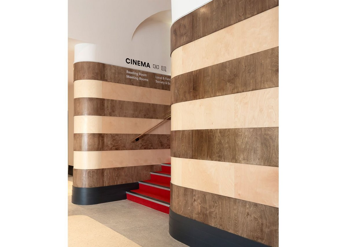 Entering Storyhouse from Town Hall Square you are drawn up into the cinema by reinstated curving stripes of ply. Chester Storyhouse, Bennetts Associates.