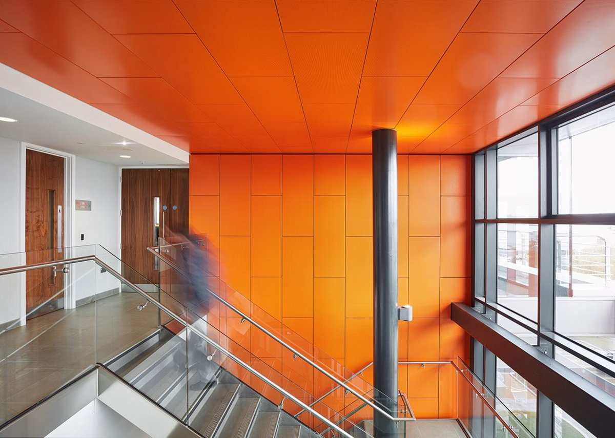 Bright orange Armstrong R-H 200 perforated metal hook-on planks on the ceiling of the Wirral Waters Kingsgate office building, Birkenhead.