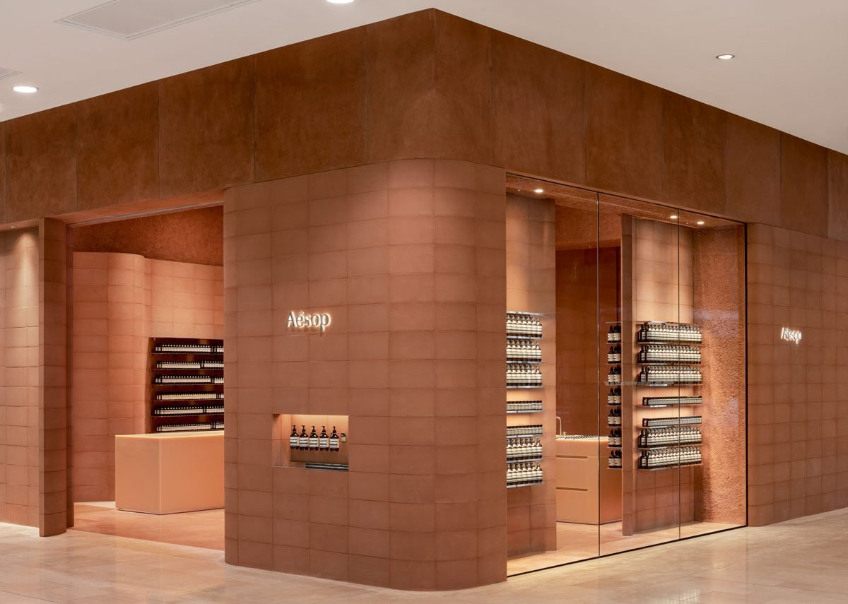 Blockwork walls tinted with red sandstone and honey-coloured resin sink units lend warmth to Aesop's Westfield store.