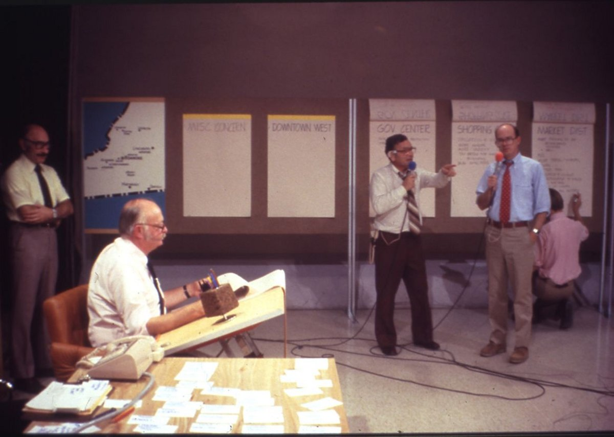 Charles Moore drafting live during a broadcast of Roanoke Design '79, while host Ted Powers and architect Chad Floyd address the camera, 1979.