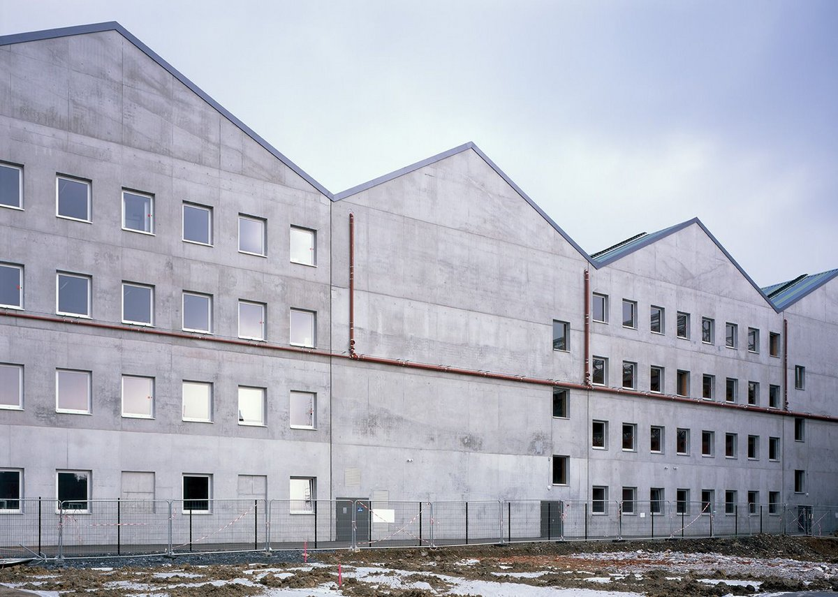 The rear of the new school is constructed from white concrete to signify where the image of the factory has been cut and changed.