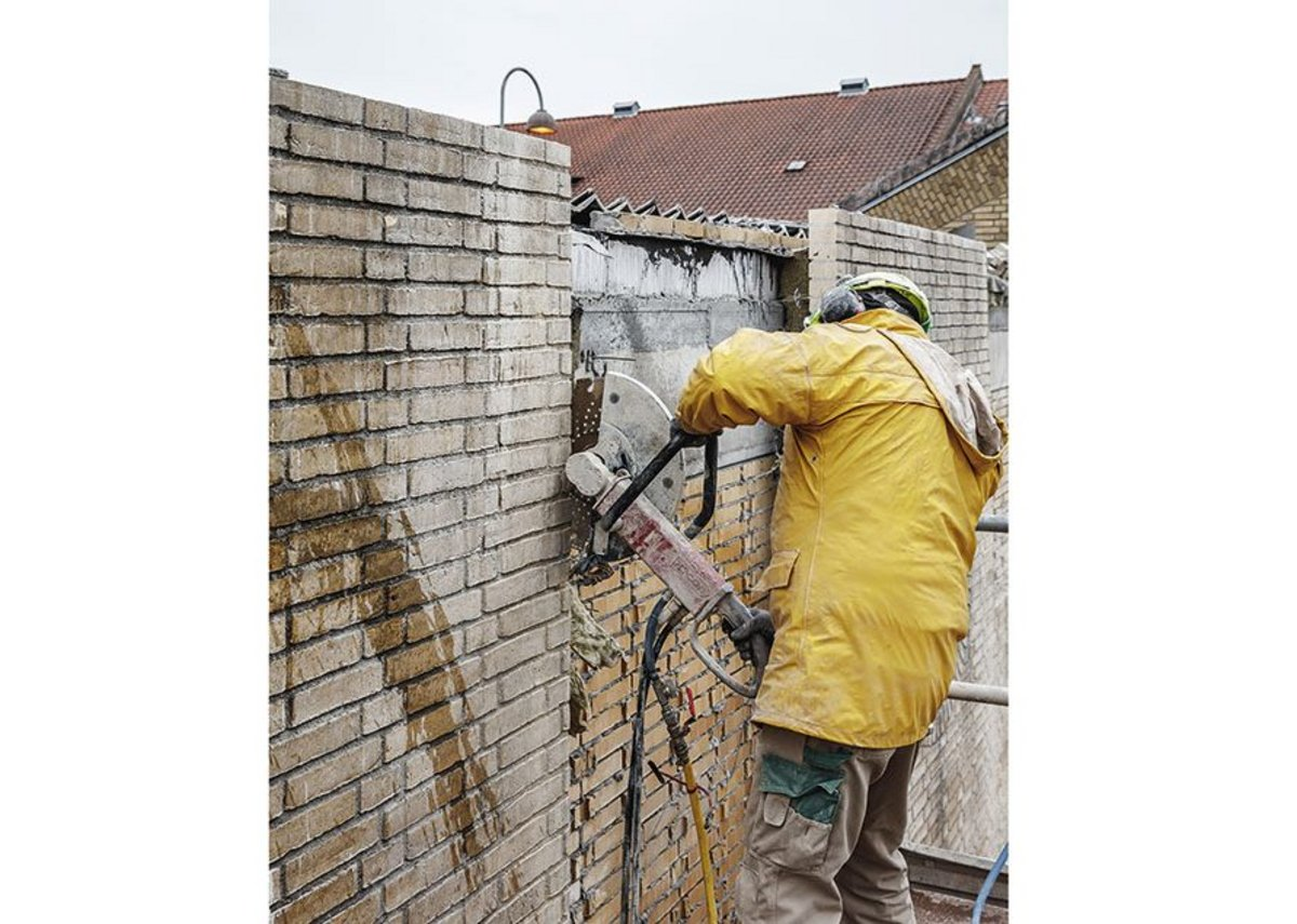 Individual sections of old wall were cut out using angle grinders.