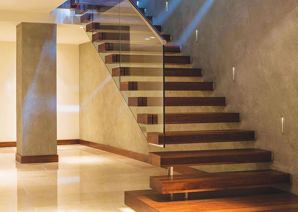Walnut cantilever 'floating' staircase with glass balustrade and stainless steel handrail.