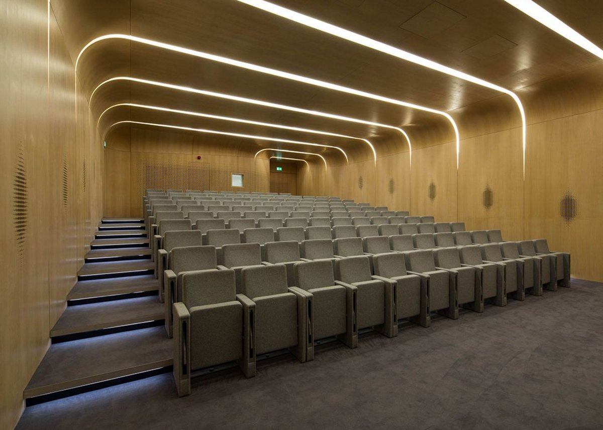 The oak-veneered auditorium, with loudspeakers behind wall perforations.