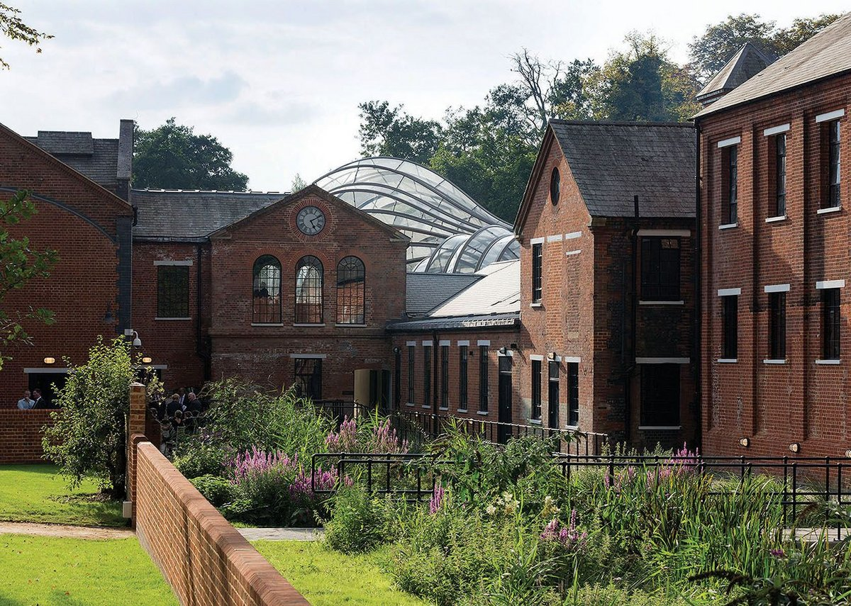 The distillery complex looking west, the curved geometry of the glass houses appearing above the original rooftops