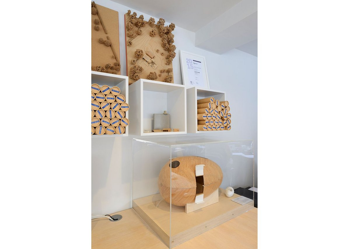 Models and rolls of drawings displayed on the shelves at PAD Studio.
