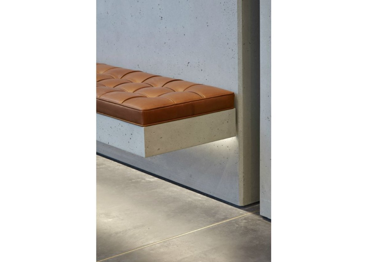 Underlit bench seating showcases polished concrete at One Bedford Avenue, Fitzrovia, London. Architect Bennetts Associates.