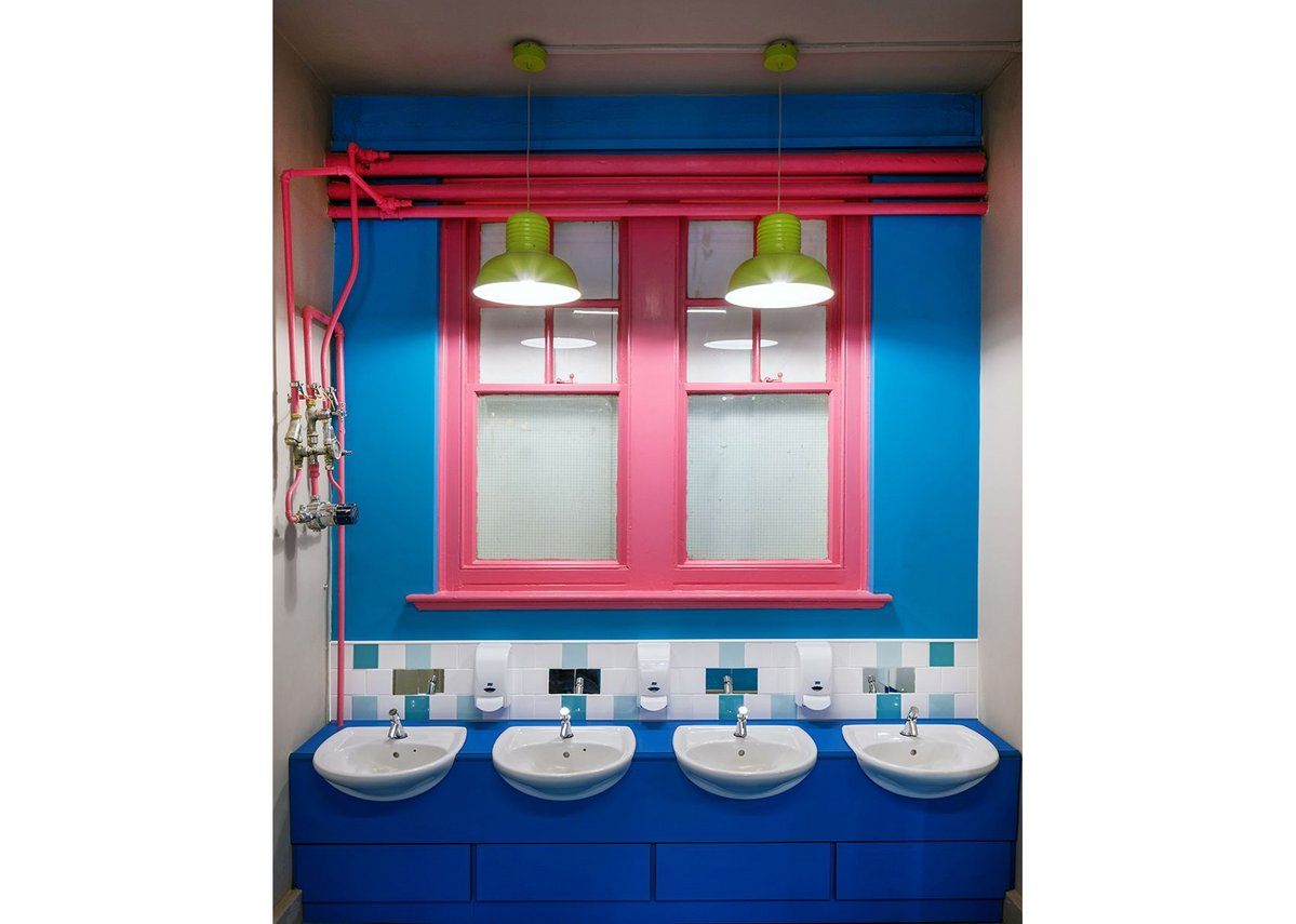 Pipework and windows in pink against the blue background of wall and floor.