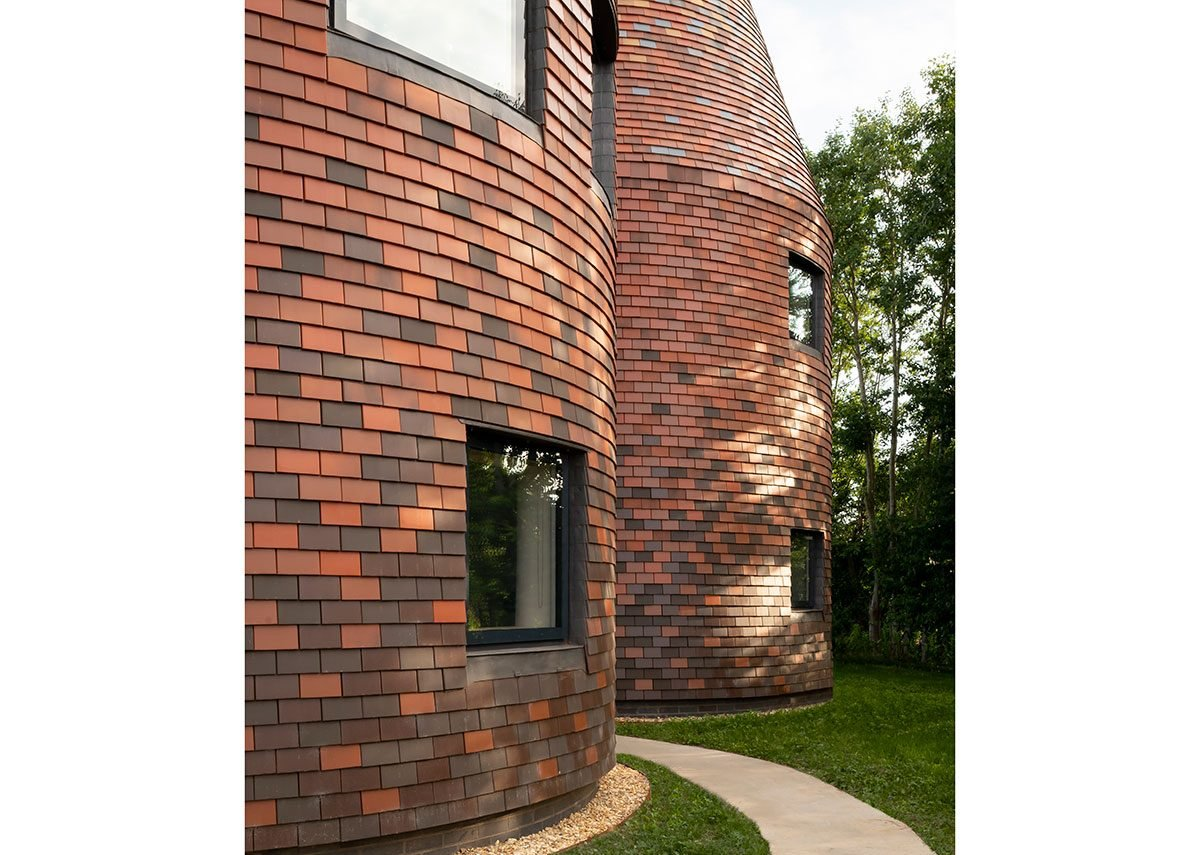 The house is entirely clad in ceramic tiles, changing from darker at the bottom to lighter at the top.