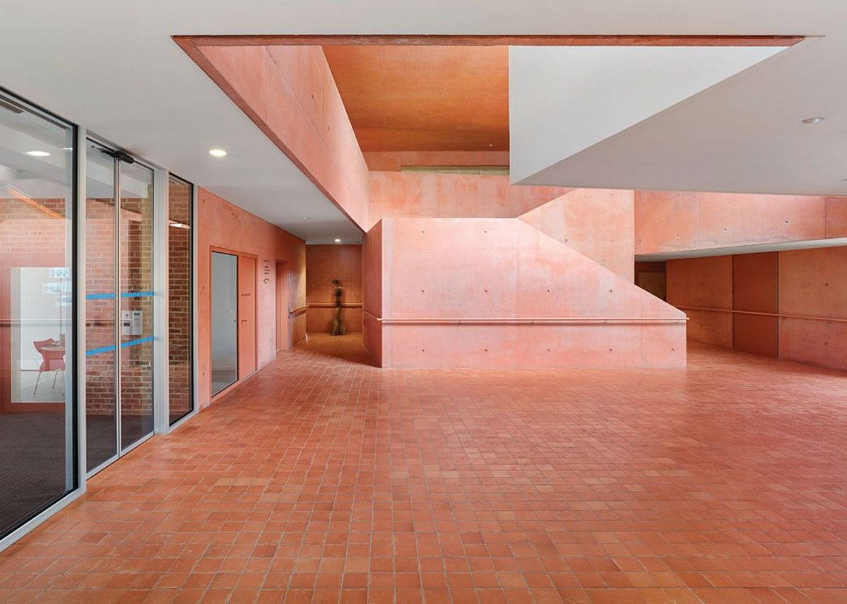 The pink tinted, sculptural concrete atrium. The terracotta floor tiles continue onto the river terrace to the right.