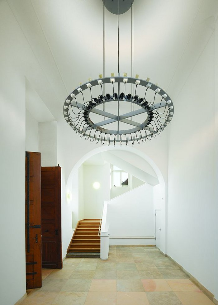 The entrance to one of the 17th century buildings that LRO has refurbished as part of the works. The light fixture designed by the firm is made of 36 'plug-in' luminaires – a sculpture formed through contingency.