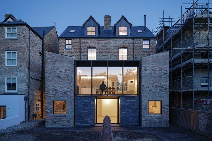The garden elevation extends both houses' rear extensions and builds between them to form one of striking, postmodern symmetry.