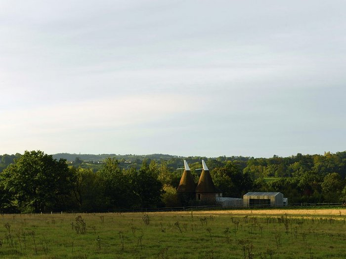 Fitting into the East Sussex landscape: a cluster of 'agricultural' buildings and two old oast houses.