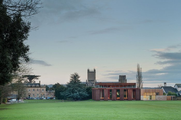 From across the cricket pitch the importance of sinking the volume of the hall into the ground, and reducing the massing at clerestory level, is clear. Left is the school's reception, right are red timber-clad music practice rooms.