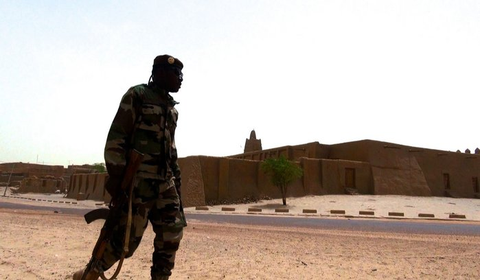 A soldier patrols in front of Djinguereber Mosque, Timbuktu.