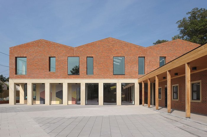 An existing adjacent block (now staff room), with its new timber colonnade and extended roof line, becomes part of the cloister composition and helps frame the playground area.